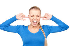 Smiling woman with fingers in ears Stock Image