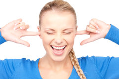 Smiling woman with fingers in ears Stock Photography