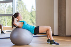 Smiling woman with fit ball flexing muscles in gym Stock Image