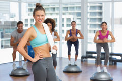 Smiling woman with fit people performing step aerobics exercise Royalty Free Stock Photography