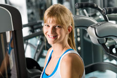 Smiling woman at fitness center exercise machine Royalty Free Stock Image