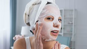 Smiling woman fixing rejuvenating cosmetic white tissue mask on face. Smiling woman with towel on head fixing rejuvenating cosmetic white tissue mask on face stock video