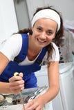 Smiling woman fixing washing machine Royalty Free Stock Image