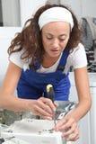Smiling woman fixing washing machine Royalty Free Stock Images