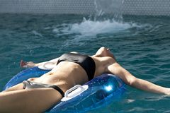 Smiling Woman Floating in Pool. Smiling female at the edge of a swimming pool Stock Photo