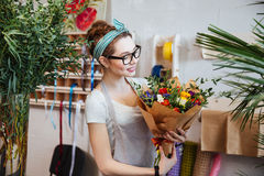 Smiling woman florist holding bouquet of flowers in shop. Smiling attractive young woman florist standing and holding bouquet of flowers in shop Royalty Free Stock Photo