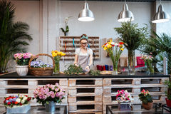 Smiling woman florist standing and working in flower shop Stock Images