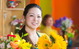 Smiling Woman in Flower Shop with Sunflowers Stock Photography