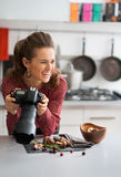 Smiling woman food photographer taking a break in kitchen Royalty Free Stock Image