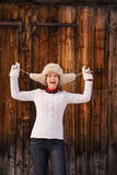 Smiling woman fooling around with furry hat near wood wall Stock Photo