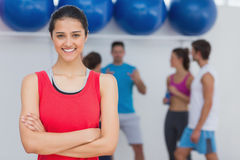 Smiling woman with friends in background at fitness studio Stock Image