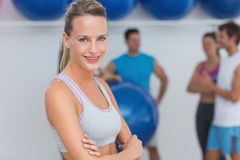 Smiling woman with friends in background at fitness studio Stock Photos
