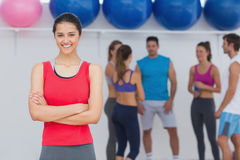 Smiling woman with friends in background at fitness studio Royalty Free Stock Photos
