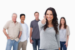 Smiling woman with friends behind her giving thumb up Stock Images
