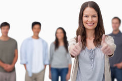 Smiling woman with friends behind her giving thumbs up Royalty Free Stock Photography