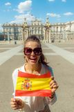 Smiling woman in front of Royal Palace showing Spain flag. Smiling elegant woman in the front of Royal Palace showing Spain flag stock image