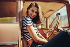 Smiling woman on front seat of a car. Smiling young woman sitting on front seat of car and looking at camera. Female on a road trip stock image
