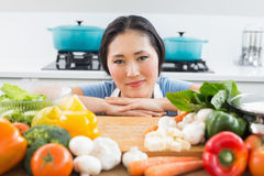 Smiling woman in front of vegetables in kitchen Stock Images