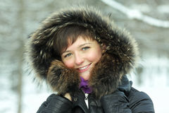 Smiling woman in frosty day hands at hood Stock Image