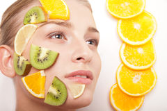 Smiling woman with fruit mask on her face isolated Stock Images