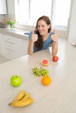 Smiling woman with fruits gesturing thumbs up in kitchen Royalty Free Stock Photos