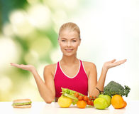 Smiling woman with fruits and hamburger Stock Images