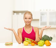 Smiling woman with fruits and hamburger Royalty Free Stock Photos