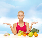 Smiling woman with fruits and hamburger Stock Photos
