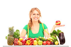 Smiling woman with fruits and vegetables holding an apple with m Royalty Free Stock Image
