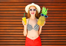 Smiling woman with funny pineapple and juice cup or smoothies. On wooden background royalty free stock photo