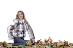 Smiling woman with fur. Sitting on autumn leaves Royalty Free Stock Photos