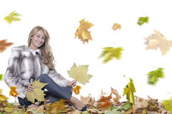 Smiling woman with fur. Smiling young girl with fur sitting on autumn leaves on the move royalty free stock photos