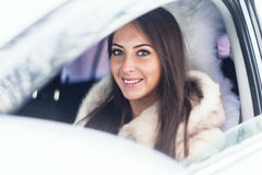 Smiling woman in fur coat sitting car Winter Stock Photo