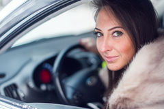 Smiling woman in fur coat sitting car Winter picture. Royalty Free Stock Photography