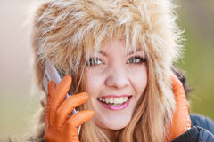 Smiling woman in fur hat talking on mobile phone. Portrait of pretty smiling fashionable woman talking on mobile phone. Happy gorgeous young girl in fur winter Stock Photo