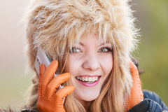 Smiling woman in fur hat talking on mobile phone. Portrait of pretty smiling fashionable woman talking on mobile phone. Happy gorgeous young girl in fur winter Stock Photos