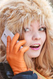 Smiling woman in fur hat talking on mobile phone. Portrait of pretty smiling fashionable woman talking on mobile phone. Happy gorgeous young girl in fur winter Royalty Free Stock Photos