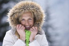 Smiling woman in fur hood in snowy outdoors Royalty Free Stock Image
