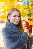 Smiling woman gathering autumn leaves Stock Images