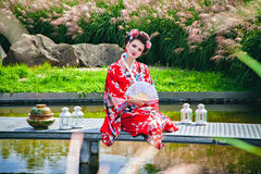 Smiling woman in geisha costume in the garden Royalty Free Stock Photo