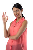 Smiling woman gesturing okay hand sign against white background Stock Photos