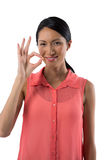 Smiling woman gesturing okay hand sign against white background Stock Images