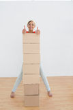 Smiling woman gesturing thumbs up with stack of boxes in new house Stock Photos