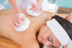 Smiling woman getting a back massage with herbal compresses Stock Photography