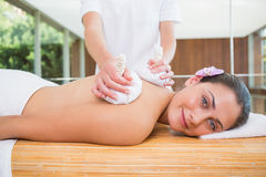 Smiling woman getting a back massage with herbal compresses Royalty Free Stock Image