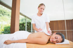 Smiling woman getting a back massage with herbal compresses Royalty Free Stock Photography