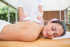 Smiling woman getting a back massage with herbal compresses Royalty Free Stock Photos