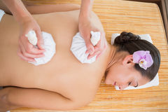 Smiling woman getting a back massage with herbal compresses Stock Photo