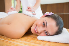 Smiling woman getting a back massage with herbal compresses Stock Images