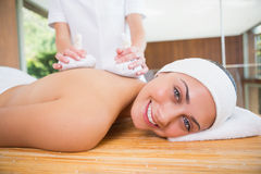Smiling woman getting a back massage with herbal compresses Royalty Free Stock Photo
